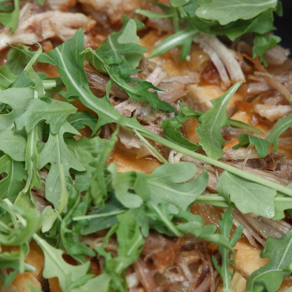 Focaccia de secreto con rúcula y cebolla a la sidra
